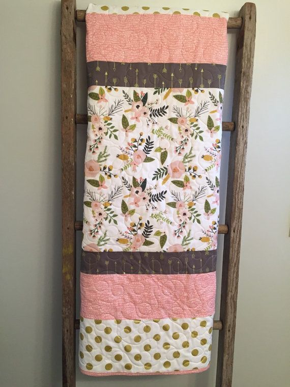 If you are looking for a simple yet stunning baby girl quilt, here it is. It is made from high quality 100% cotton designer fabrics featuring floral sprigs, and metallic gold arrows and dots. With shades of blush, pink, greens, gray and gold it would be a beautiful addition to that special modern little girls nursery. Need a larger size instead? No problem, just send me a convo and I can set up a custom listing for you.  This generously sized quilt is constructed of three layers with…