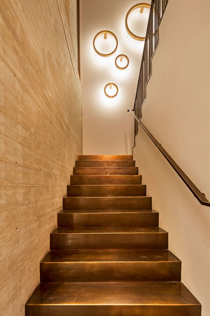 In This Modern House, A Staircase With Bronze Stairs And A Concrete Wall  Leads You