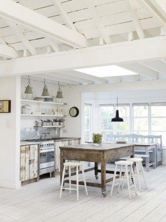Droomkeuken: Het landelijke en industriële komen hier goed samen in deze white wash keuken met een wit geverfde houten vloer, sloophouten kastjes en fabriekslampen.