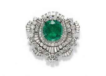 An emerald and diamond clip brooch, signed Bulgari. Photo Christie's .  a motivo di coccarda con smeraldo centrale taglio cuscino incorniciato da brillanti e diamanti taglio baguette in file alternate, datata 1950; smeraldo cts 13.67