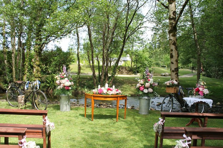 Ceremony table with unity arrangement, framed by a large floral arrangement in milk churns and vintage bicycles
