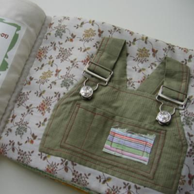 The book is made out of old clothes and teaches a child how to use zippers, buttons, snaps, and hooks on clothing. Can use those baby girl clothes that I can't throw away, but have no use for