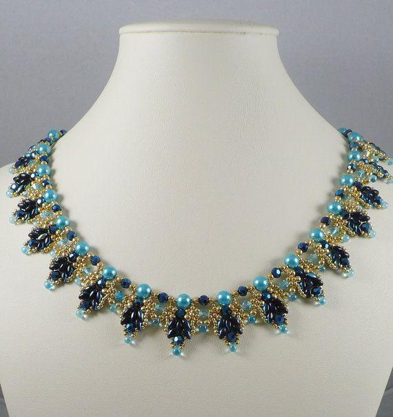 Questi gemelli di vetro blu evidenziato getto perline si intrecciano in un bordo smerlato con minuscoli permanente finitura branelli del seme dorato