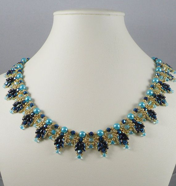 These blue highlighted jet glass twin beads are woven into a scalloped edge with tiny permanent finish golden seed beads and light aqua crystals