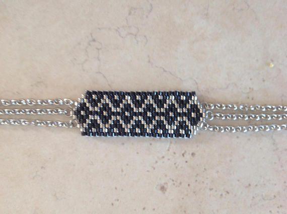 Bracelet en perles MIYUKI 11 délicas noir et argent Tissage à la main avec une aiguille Dimensions hors accroche : 4 x 1,5 cm Fermoir mousqueton et chaîne acier inox Longueur : 17 cm Vous pouvez lavoir dans la longueur que vous désirez , il suffit de me le préciser à la commande