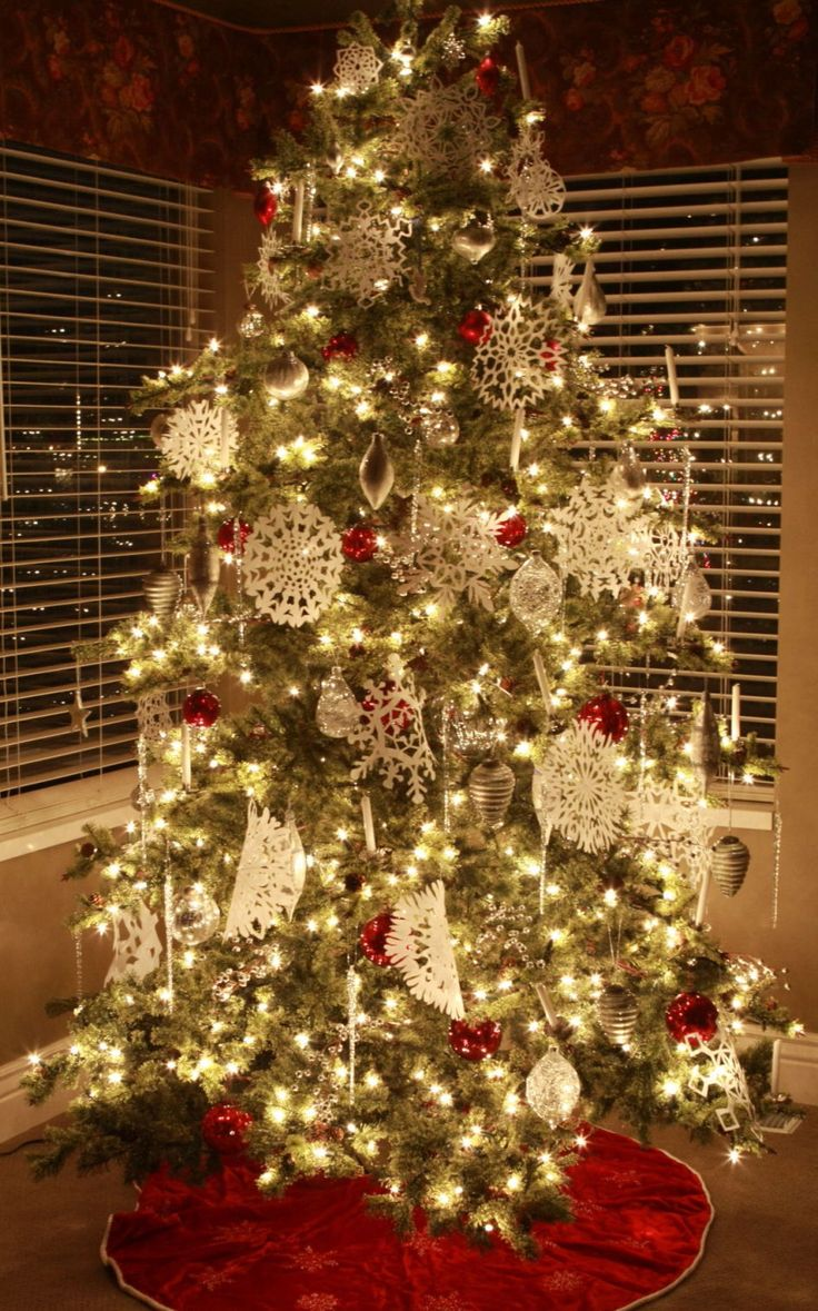 Decoration red christmas tree skirt and hanging snowflakes also white balls plus stunning indoor christmas