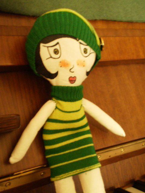 Bambola di pezza con tubino a righe.