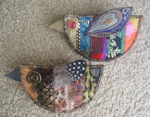 Fabrics used are scraps of silk on the top one, and faux leather animal prints on the lower one.  Seams are covered by sewing on bits of ribbon, trim and fibers.  I used a real feather for the wing on the lower one.: