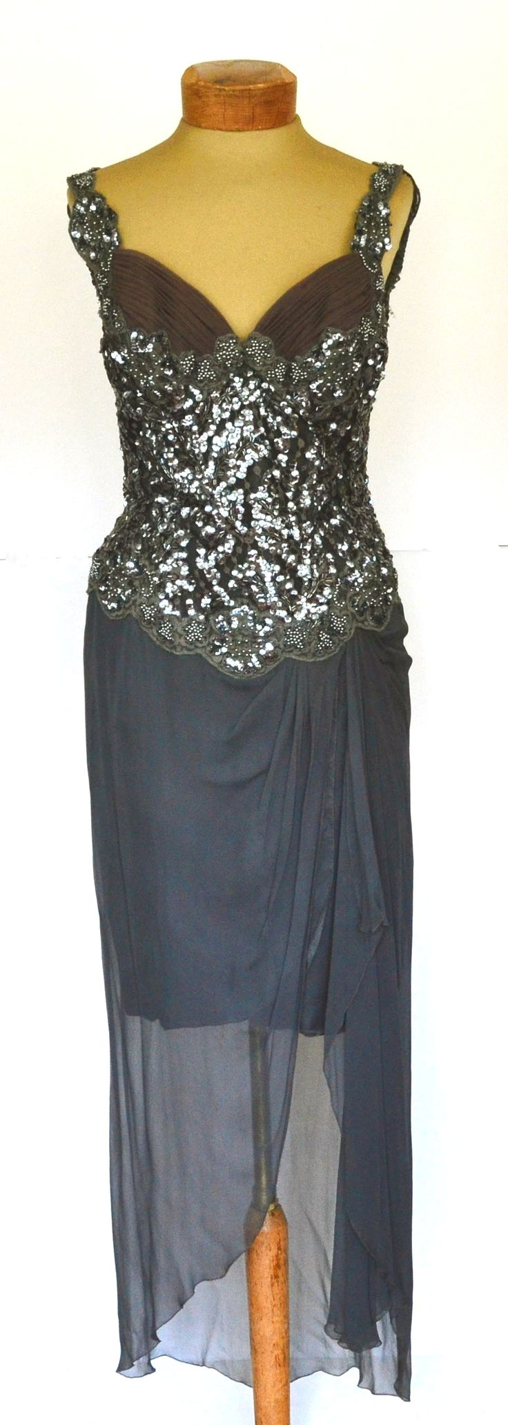 Be a knock out in this vintage sequined dress! Sequins are festive, and fun, chiffon is feminine, and soft, and a low ruched bust-line is sexy! A great combination! The unique skirt of this vintage Bergdorf Goodman dress hits at knee, with a longer layer of sheer chiffon over that gathers off center. Very intriguing.  This vintage 1990s dress has a fully sequined bodice in gray and silver beads and sequins. Ruched, and gathered mesh bust in a sweetheart neckline. Sequined shoulder straps ...
