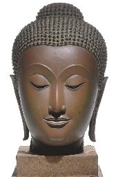 A bronze head of Buddha Thailand, Ayutthaya, 15th/16th century The oval face with serene expression, crisply and sensitively delineated lips, straight nose joining arched brows, the heavy-lidded eyes cast downward, framed by delicately curved eyebrows echoed by the hairline, with remains of lacquer in the eyes and gilding all over 12 in. (30.5 cm.) high
