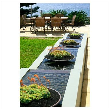Contemporary sloped water rill with containers planted for Garden features australia