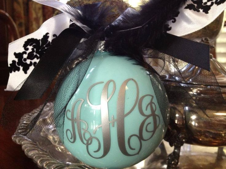 """Monogram Ornament. I put Martha Stewart SURF paint inside the bulb, making sure to evenly coat the entire inside of the bulb. Once coated, I left upside down overnight to dry, sitting on a cup. Added my monogram (with silver vinyl), added the ribbons and feathers... there's a """"blow by blow."""" The font is monogram KK."""