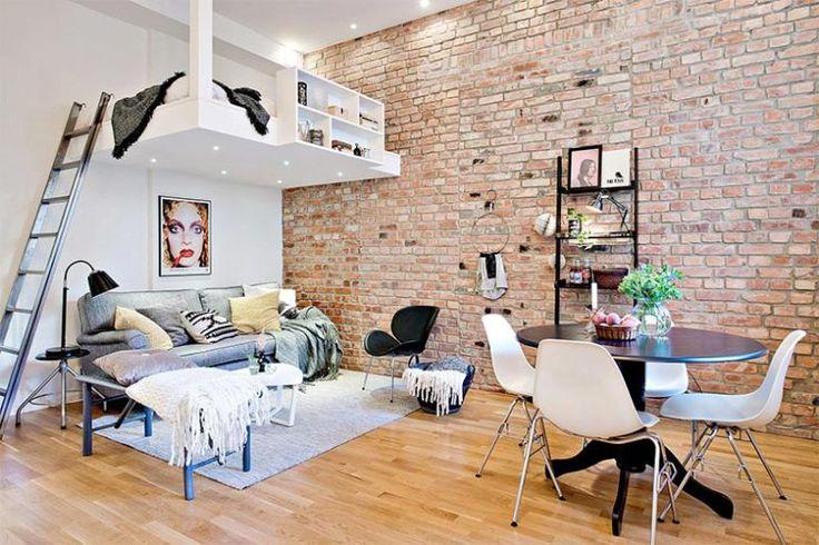 A cama suspensa foi uma solução para economizar espaço na quitinete de 32 m² e a parede de tijolos de demolição ajuda a tornar o ambiente mais aconchegante.