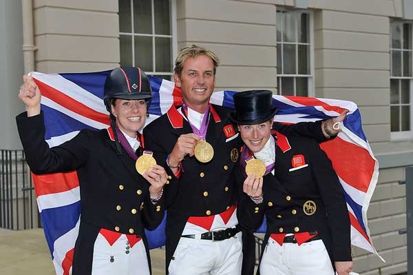Great Britain's Dressage riders scooped Olympic team gold. Carl Hester, Laura Bechtolsheimer and Charlotte Dujardin bring spectators to their feet in celebration of the first-ever British Dressage medals in the history of the Games.    http://api.ning.com/files/nZO0Nepq2fyD3ZkD0ftAV2Jm03sAR4a6NrskNCyT3b*lJ-sjyoTF1XNLTZejDXgNl24PGxh2GmSxZiNrVhK1h-H6jq6PXYqD/8712OlympicDressTeamGB.jpg