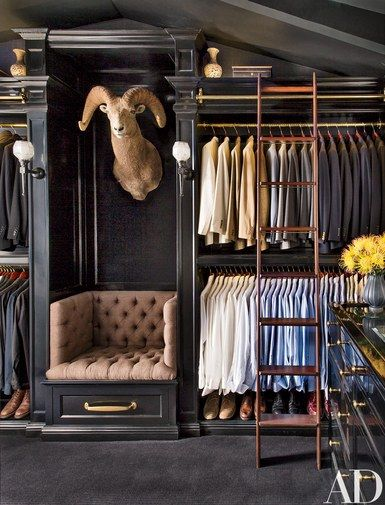 Vintage sconces from Liz's Antique Hardware are mounted alongside a taxidermy ram's head; the seat is clad in suiting fabric, and the ladder was custom made by Putnam Rolling Ladder Co. | archdigest.com