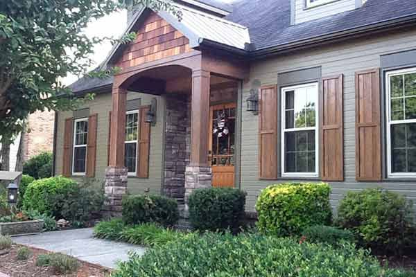 These homeowners loved the lines of their simple Cape Cod, but wanted a more modern feel. They covered the existing porch, added columns of cedar and stack stone, put in a new stone border around the front, and added shutters to the window for a more inviting facade.