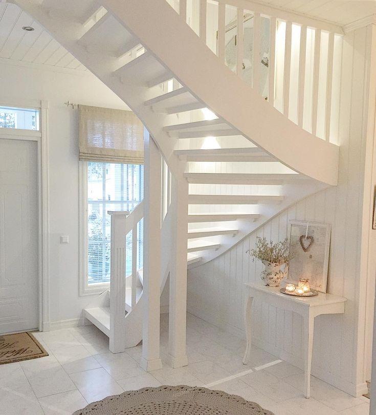 Valkoisen eteistilan portaikon alle kätkeytyy kiva pieni pöytä arjen tarpeistolle ja koriste-esineille