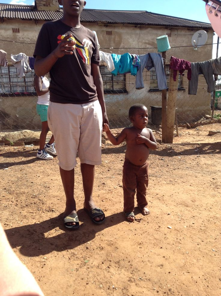 In South Africa there are these tin shack communities called informal settlements or Mkuhkuhs. In these communities, everyone looks after each other and makes sure they are healthy and safe. In this picture a boy was running around our group so one of the guys that was giving us a tour settled the kid down and and made sure he didn't wander off with us as we walked on through the Mkuhkuhs.