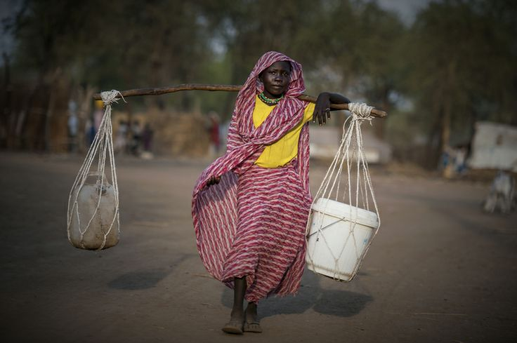 A South Sudanese woman carries her worldly possessions after fleeing violence in northern Sudan.  Photo by Sebastian Rich.  #Sudan #refugees #WorldRefugeeDay