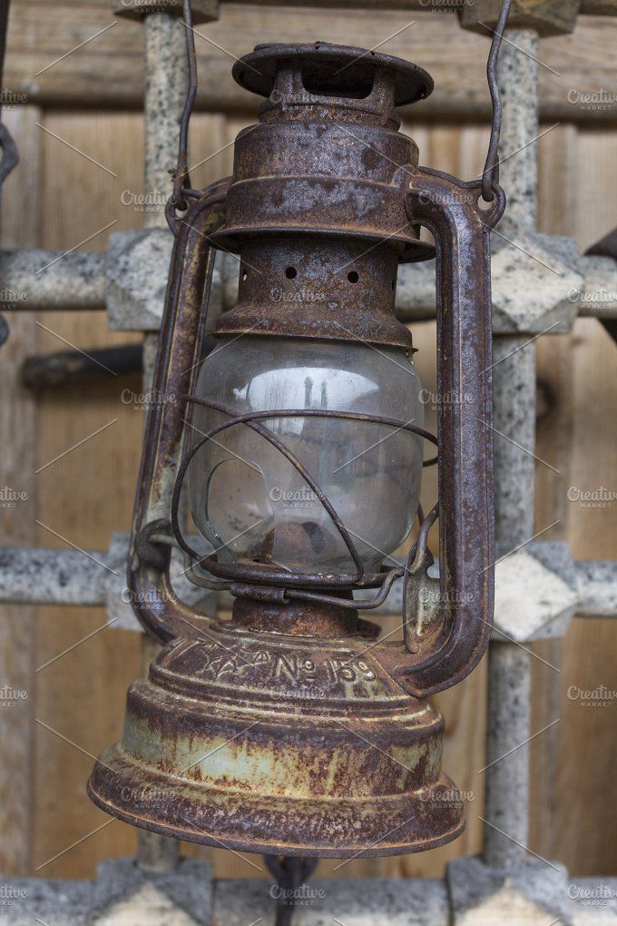 Old kerosene lamp hanging on a metal grid by Koriza on @creativemarket