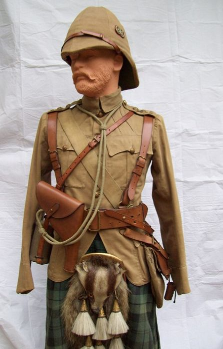 """A Captain of the Argyll & Sutherland Highlanders as he might have appeared in South Africa 1899-1902. He wears a khaki drill doublet with gauntlet cuffs, helmet with khaki 6 panel cover and regimental badge or """"flash"""" on the left side consisting of an o/r's collar badge on a red Melton cloth backing. His beautiful honey colored Sam Browne belt, haversack and water bottle are all provided by Hobson and Sons, and his helmet is by Hawkes & Co. (Photo: James Holt collection)"""