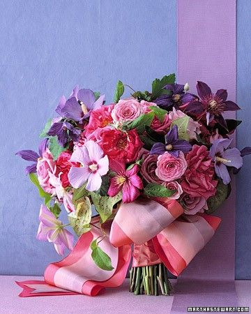 A bouquet that combines roses with seasonal blooms and greenery will have a fresh-from-the-garden feel. Here, these late-summer purple clematis, pale hibiscus, and fuchsia-speckled caladium leaves surround luxurious Dutch and garden roses. One vintage silk ribbon overlays another to form a billowy bow.