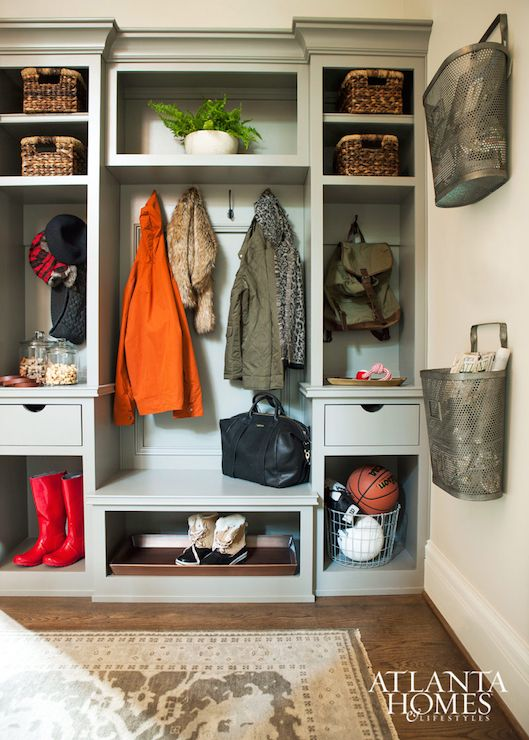 Transitional mudroom features gray built-ins filled with wicker baskets and backpacks flanking a built-in bench under a row of hooks alongside cubbies housing shoes and boots alongside metal wall baskets filled with magazine and books.