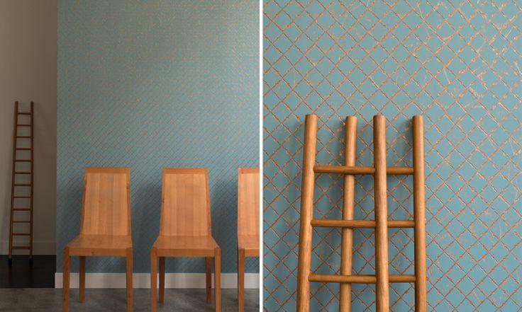 Un muro quadrettato da piccole piastrelle smaltate, patinate, smussate, con tonalità metallizzate, ramate e colori opachi.     <br>