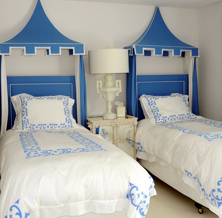 Greek bedroom boasts blue headboards on twin beds dressed in white and blue bedding adorned with blue canopy accented with white and blue bed panels flanking a shared seashell encrusted mirrored nightstand topped with white urn table lamp.