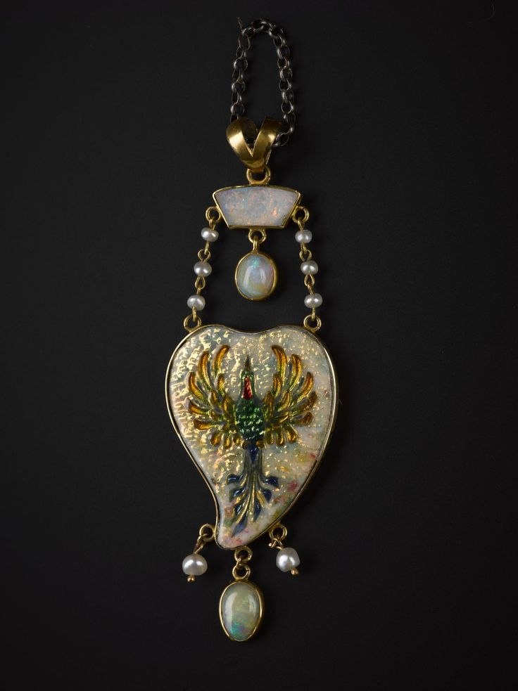 Heart shaped pendant of gold, enamelled and bearing a bird design, set with pearls and opals and with a gold suspension loop: Scottish, Aberdeen, by James Cromar Watt