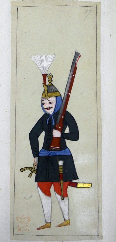 Cebici. A foot soldier of the old corps of armourers attached to the Janissaries. Helmet has a long plume-holder containing a stiff plume. The helmet fits over a blue cloth which is tied over the head and knotted under the chin. Silver helmet with gold brim and top. Stubble on his chin. Holding a matchlock, he is wearing a green tunic, blue kuşak with a knife in a case (kârd), a sword, high white leg protectors, red trousers and yellow shoes.