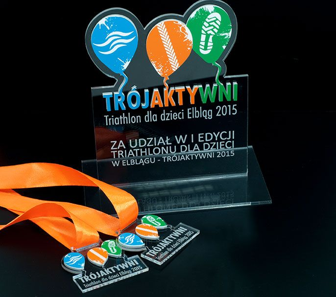 A memorial statue and medals for taking part in the first edition of Triathlon for children in Elblag - Trójaktywni 2015. Statue of sports and medals were made ​​of a combination of two materials - plexiglass elegant and modern laminate engraving . Acrylic transparent engraved . Engraving laminate color - blue, orange and green. Statuette sports - elegant , interesting colors , stable and impressive .