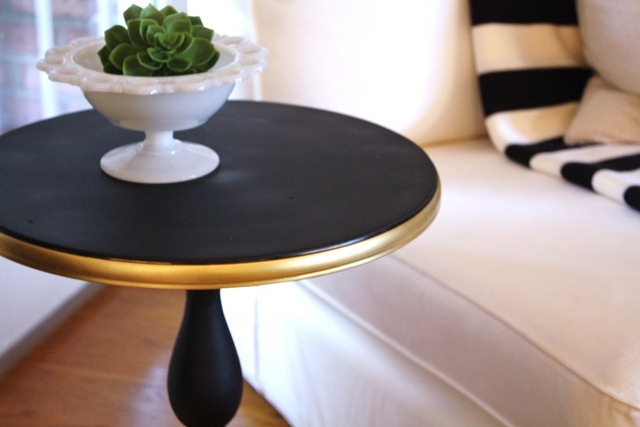 Paint a side table flat black and edge in metallic gold.