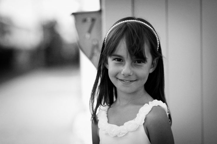Flower girl at a wedding at home at Milford beach, Auckland. Black and White.  beguiling fine art family photographs for the walls of the most discerning clients homes. We specialise in wedding and family portrait photography, and supply prints on the highest quality media, framed in beautiful conservation standard frames. We are a high end studio located in the beautiful city of Auckland, New Zealand.