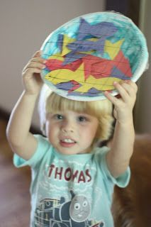 """For the """"Breakfast on the Shore"""" or large catch story in John 21. Child paints paper plate, fills it with paper fish, covers the plate with clear wrap and then draws on the net using a sharpie marker. Cool."""