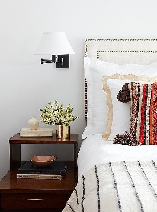 A headboard accented with brass nail heads is a polite nod to tradition—and proof that beige can be beautiful, especially when it's loved and layered.