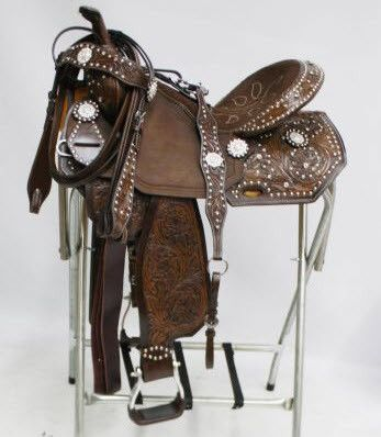 This New, One of a Kind, beautiful Barrel Saddle Set features dark floral tooled leather accented with silver studs and silver crystal rhinestone conchos. Saddle comes equipped with leather latigo and