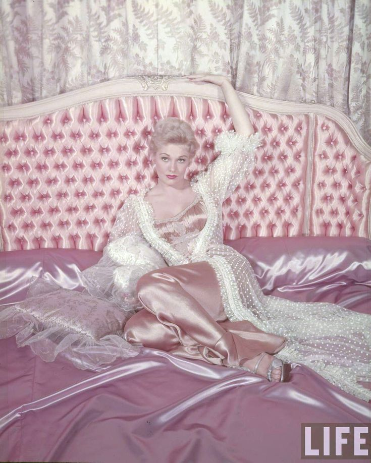 Kim Novak on an amazing pink tufted and gleaming satin bed.