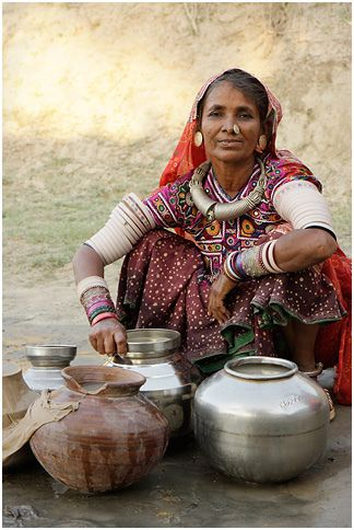 *A kutchi woman posing with her water filled pots at the village well for which sometimes they have to walk miles and miles
