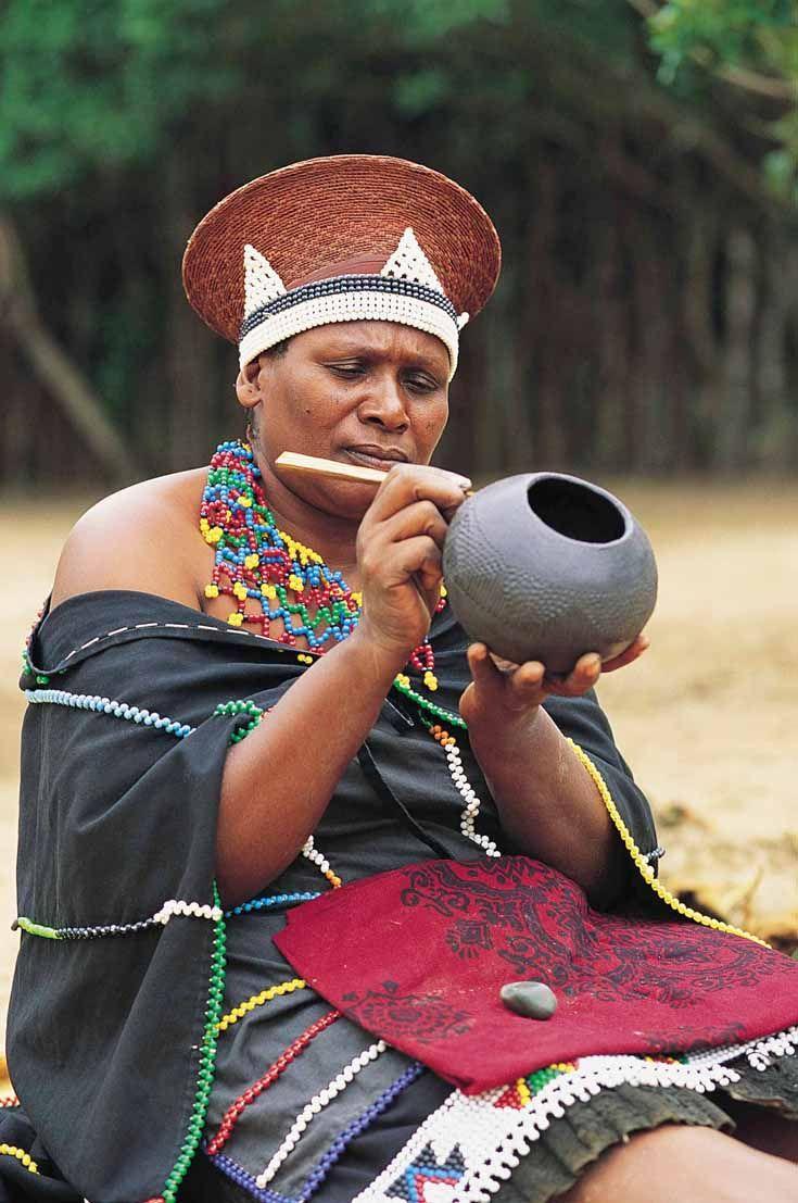 Zulu traditional dress in zulu kraal kwazulu natal - Africa A Married Zulu Woman Wearing A Traditional Hat Cloak And Necklace Is Painting