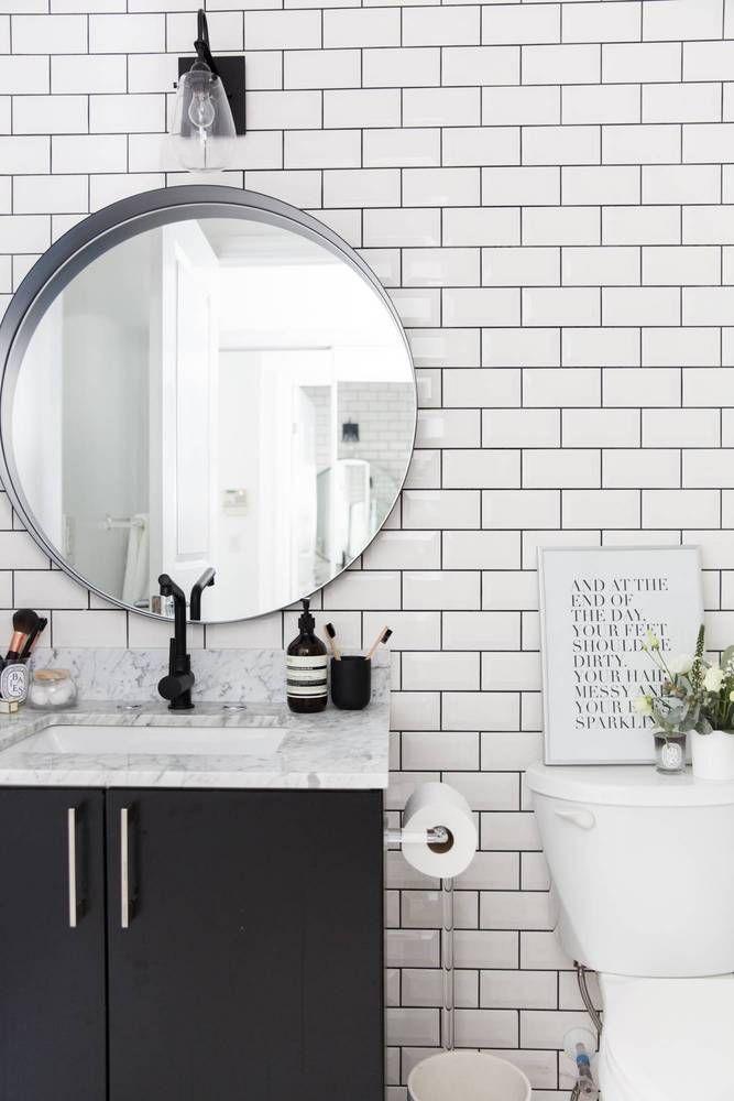 white subway tile on bathroom wall/black vanity/round mirror/marble top vanity