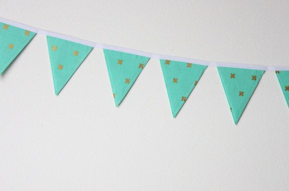 XOXO Mini Fabric Bunting. Fabric bunting can be used over and over again! Party decorations, nursery or kid's room decor, over a doorway or around a window, the options are endless! This bunting features a turquoise fabric with metallic gold X's. #theevergreencollective