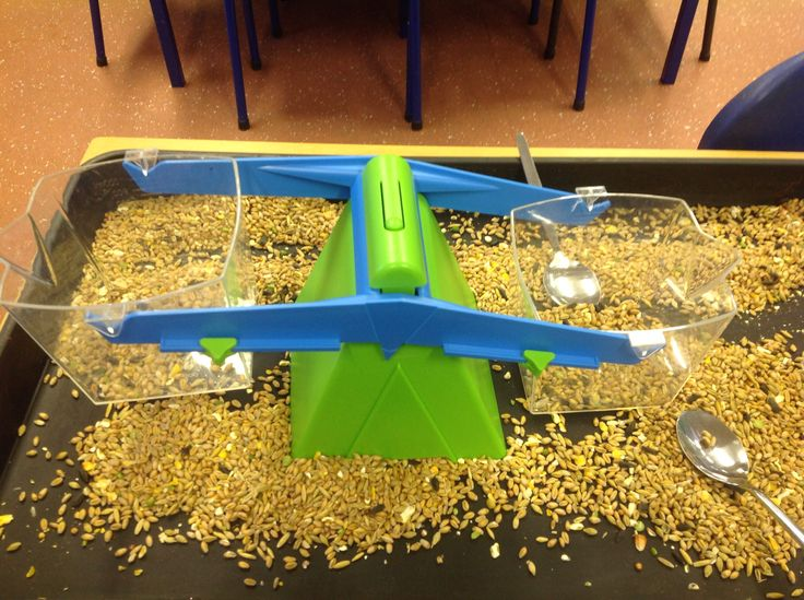 Exploring weight and capacity by weighing out bird seed in the sensory tray. Great for developing mathematical language in EYFS