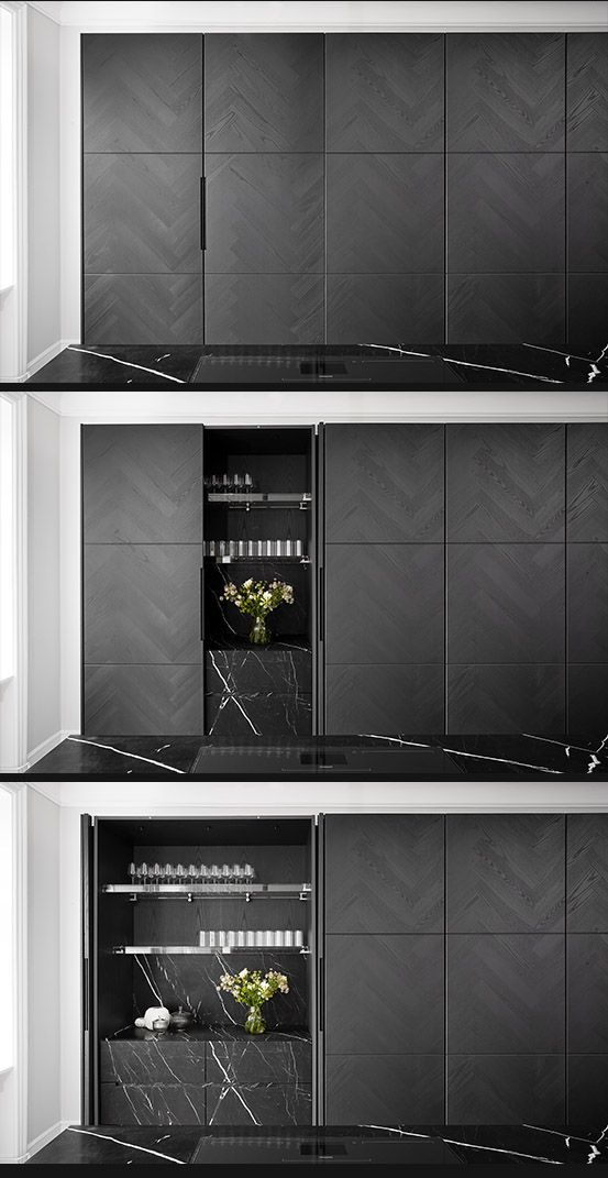 Vinculum, contemporary kitchen design from piqu. Featuring tall units in grey ash herringbone veneer with pocket doors opening onto acid etched nero marquina stone drawers with Monolith detailing.