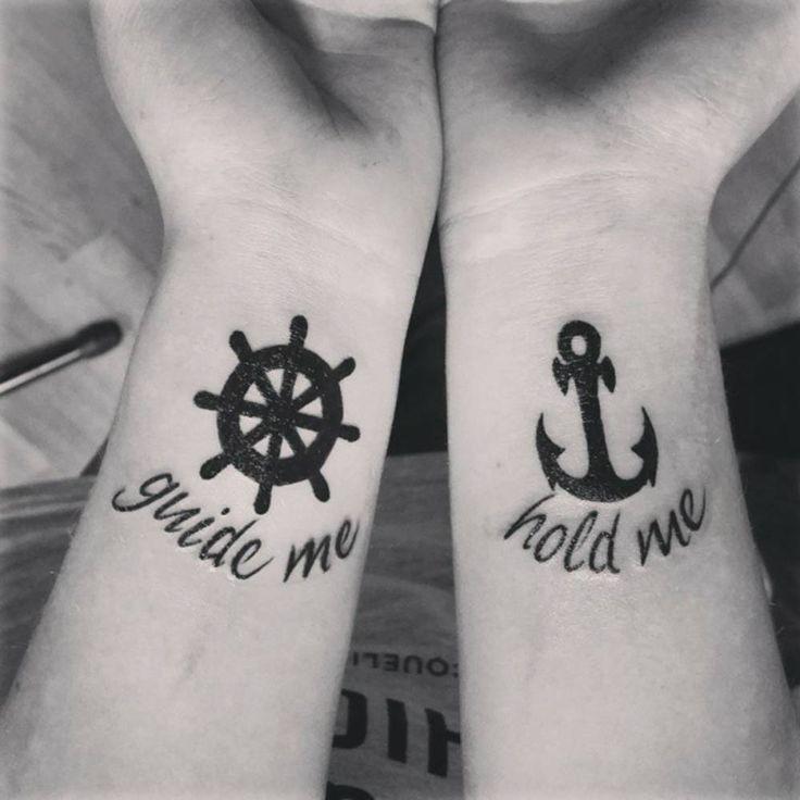 """Pequeños tatuajes de un timón y un ancla, con las frases """"Guide me"""" y """"Hold me"""" debajo de ellas respectivamente, frases en inglés que quieren decir """"Guíame"""" y """"Agárrame"""", situados en las muñecas de Nanz."""