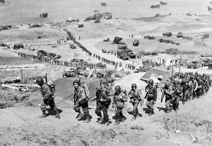 Des renforts de l'armée américaine grimpent une colline près d'un bunker allemand dominant Omaha beach après le Débarquement à Colleville-sur-Mer le 18 juin 1944.