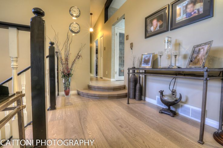 The entry of this beautiful Home features Lauzon Flooring Fifth Avenue Wire Brushed hardwood flooring from the Urban Loft Series. #interiordesign #hardwoodfloor #artfromnature #entry #hall