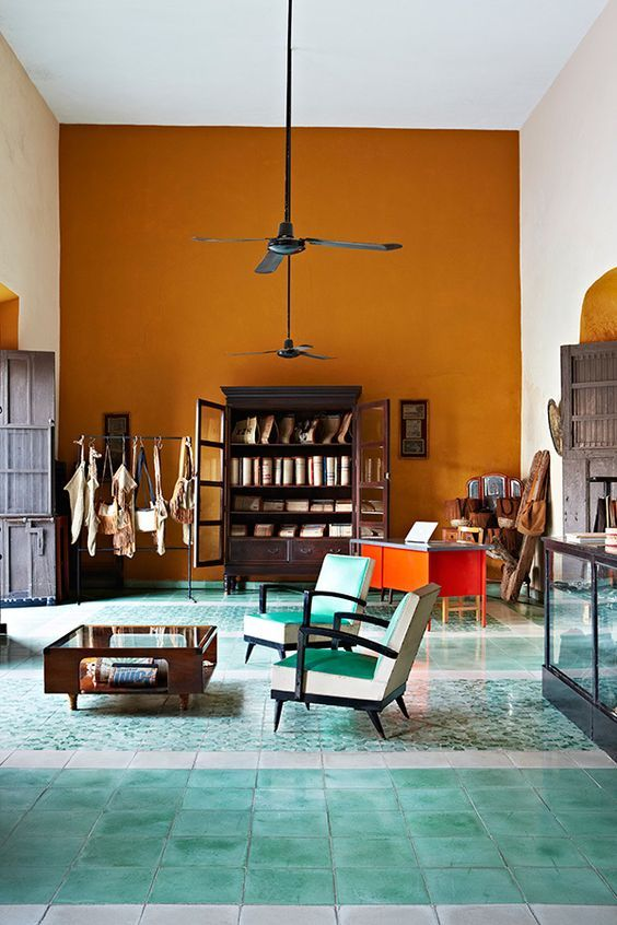 vivid colour blocking | amber orange statement wall and seafoam floor tiles | an eclectic mediterranean mix | blue midcentury armchairs and coffee table | rustic armoire | high ceilings and ceiling fans | via Armelle Habib Photography