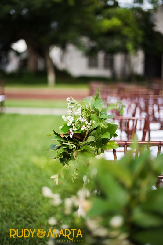 lush pew markers of magnolia, lemon leaf,elm, fern and spirea for the outdoor aisle on a spring wedding day.