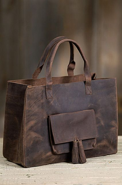 Black-oiled cowhide leather with a smooth, distressed finish, sports sturdy leather handles for hand or shoulder carry. Free shipping + returns.